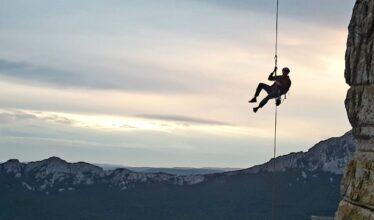 grimpeur suspendu au bout d'une corde le long d'une falaise