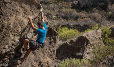 un homme escalade un rocher
